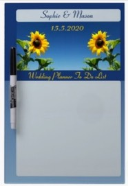 A wedding planner board. A dry erase board with sunflowers against a blue sky with the couple's names and space for the things to do before the day they say 'I do'